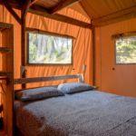 Slaapkamer in de tent, met een tweepersoons bed inclusief beddengoed.