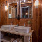 Twee wastafels met spiegels op een houten meubel en houten wand.