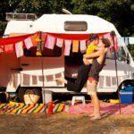Een jongen en meisje omhelzen en zoenen elkaar voor een wit oud kampeerbusje dat versierd is met zelfgemaakte slingers aan de luifel.