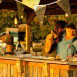 Twee vrouwen staan achter een houten buitenbar en drinken samen een biertje.