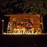 In het licht van veel waxinelichtjes zitten twee muzikanten op de veranda van een houten boomhut in het donker muziek te maken.