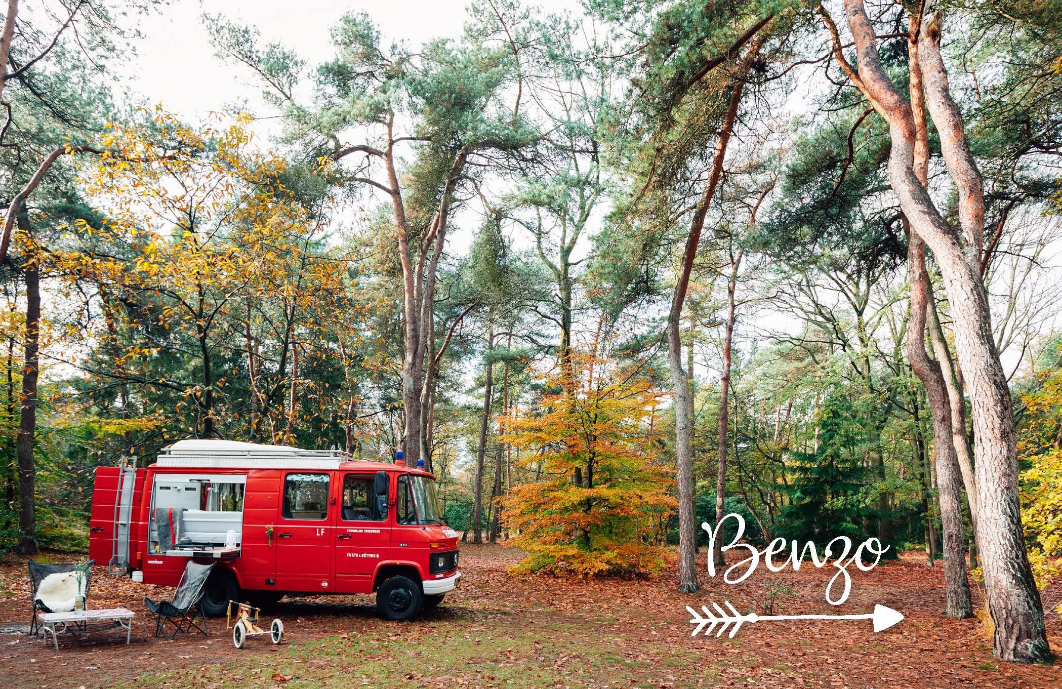 Rode oude brandweerwagen omgebouwd als camper, staat in het bos