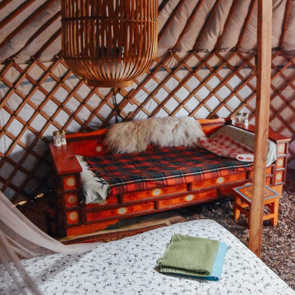 Het kleurrijke interieur van een Mongoolse ger, met bank, bontje