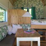 Tafeltje met bank en bed, kussens met groene bladeren, behang met bladeren. Natuur look & feel in een tiny house.