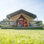 Een safaritent met houten veranda en de tentdeuren geopend