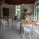 Houten tafels en witte stoeltjes in het restaurant van Erfgoed Bossem