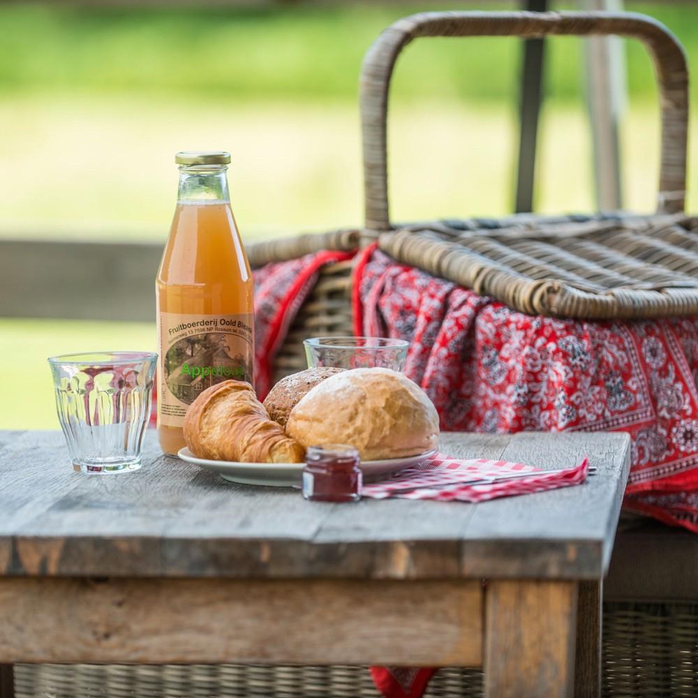 Een ontbijtmand met rood-witte zakdoek erin, broodjes en een fles pure appelsap
