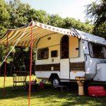 Een ouderwetse KIP caravan in bruin wit, met gestreepte luifel