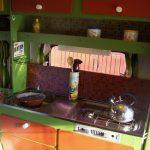 Groene keuken met groene tegeltjes, en oranje details