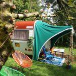 Een vintage caravan met groene luifel op de camping