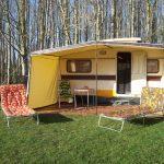 Een vintage caravan aan de bosrand, met twee 70-er jaren ligstoelen met bloemen