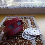 Een vintage kijker met dia schijven, op een tafel met een geborduurd kleedje