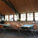 Tafeltjes en stoelen voor de ramen in het eethuisje van de Voscheheugte