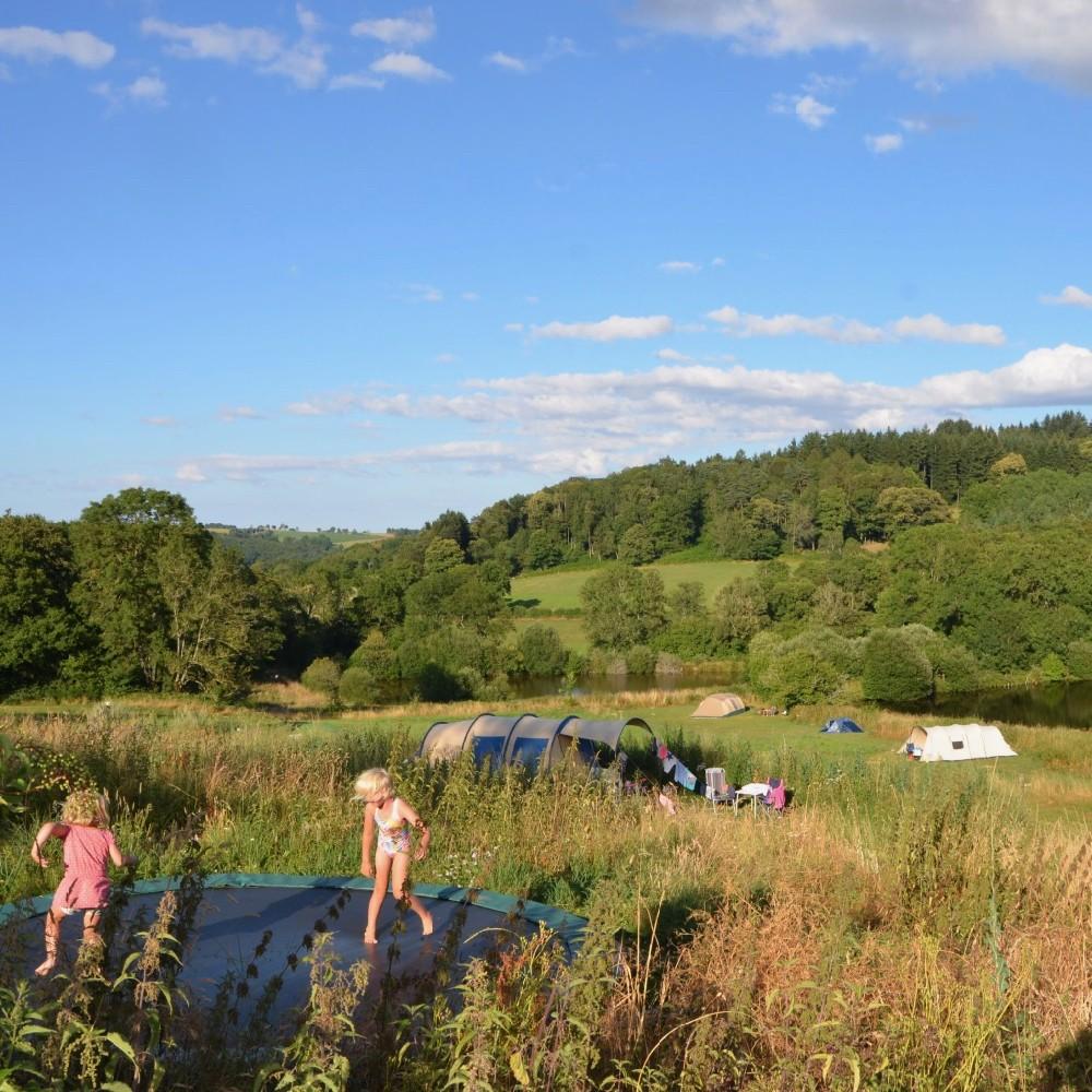 Een trampoline met springende kinderen en tenten in het veld