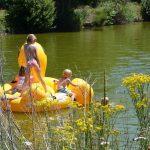 Geel opblaas speelgoed in het water met spelende kinderen