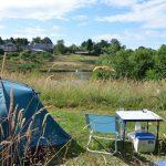 Camping 3Etangs ligt aan drie meren. Een blauwe tent met tafel en blauw stoeltje in het gras