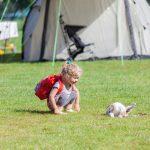 Een klein meisje zit op haar hurken naar een poes in het gras te kijken