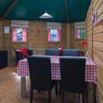 Een eettafel met vier stoelen in een zeshoekige kampeerbungalow