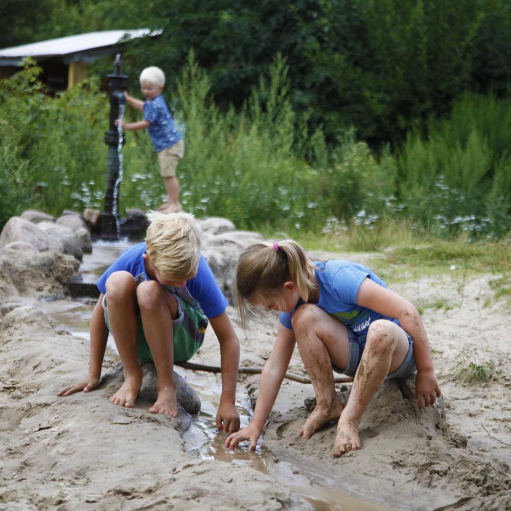 3 kinderen spelen met de waterpomp en het zand.
