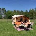 Een vintage caravan met luifel en stelletje ervoor