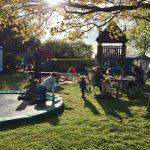Trampoline en speelhut met spelende kinderen