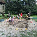 Speelplaats met zand en water en spelende kinderen