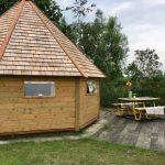 Een houten 8-hoekig huisje met een picknicktafel ervoor