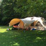 Tunneltent met grote luifel op een kampeerveld
