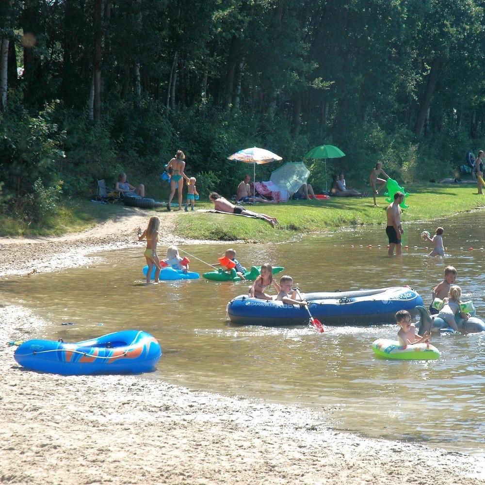 Recreatievijver met rubberen bootjes en een strandje