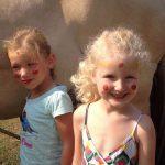 Twee blije meisjes, geschminkt met rode stippen