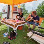 Twee mannen bij een vintage caravan zitten onder een gele luifel gitaar te spelen