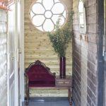 Houten sanitair gebouw met vintage bankje en bos takken in een vaas