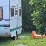 Ouderwetse caravan met oranje stoelen ervoor