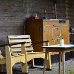 Een zitje met twee gele houten stoelen en een vintage kast
