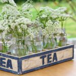 Witte veldbloemen in glazen flesjes in een houten kistje met TEA erop