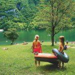 Twee meisjes met zwembanden en een rubberboot aan de waterkant op het gras