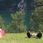 Een rode koepeltent met twee stoelen aan de rand van het meer