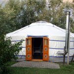 Een witte yurt met oranje deuren en een kachelpijp