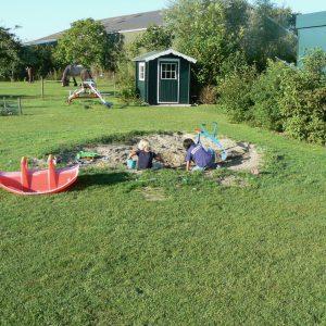 Een zandbak met spelende jongens en een rode wipwap