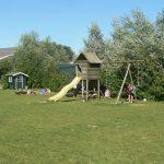 Een speeltoestel op een grasveld, bij de camping