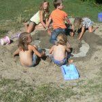 Spelende kinderen met zomerkleding in het zand met water