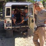 Een jeep met de achterdeur open, volgeladen met blije kinderen