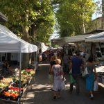Een streekmarkt in Italië, in Le Marche, met witte kraampjes en winkelende bezoekers.