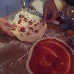Twee pizza bodems worden belegd met lekkers