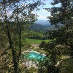Doorkijkje tussen de bomen door naar het zwembad in de heuvels van Le Marche