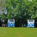 Twee houten volkswagen busjes op het kampeerveld