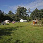 Een kampeerveld met speeltoestel, gras en veel ruimte