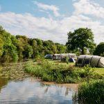Tunneltenten en caravans aan de rand van rivier de Vecht