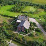 Het woonhuis met B&B en de kampeerweide van De Torenvalk van bovenaf, omringd door groen.