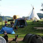 Een kampeerveld met tenten en een tipi